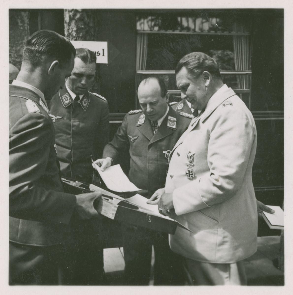 One side of a stereograph of Hermann Goering, Ernst Udet, and other Nazi military officials.   Original caption in German reads:  Der geniale Schöpfer und Oberste Befehlshaber der Luftwaffe, Reichsmarschall Herman Göring, mit Generaloberst Udet