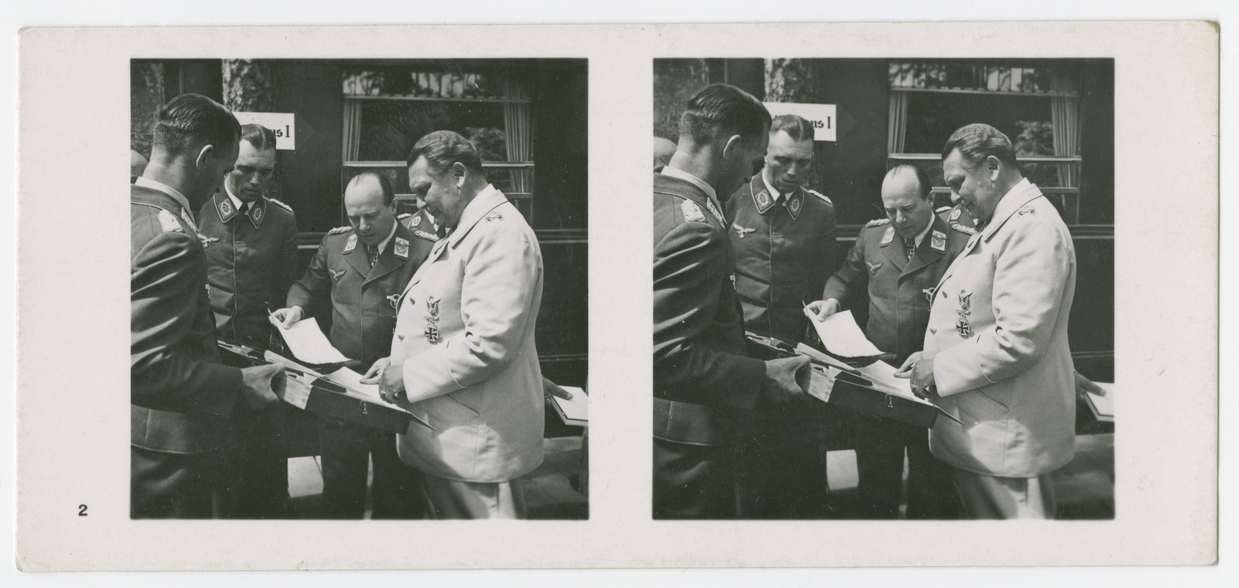 A stereograph of Hermann Goering, Ernst Udet, and other Nazi military officials.   Original caption in German reads:  Der geniale Schöpfer und Oberste Befehlshaber der Luftwaffe, Reichsmarschall Herman Göring, mit Generaloberst Udet