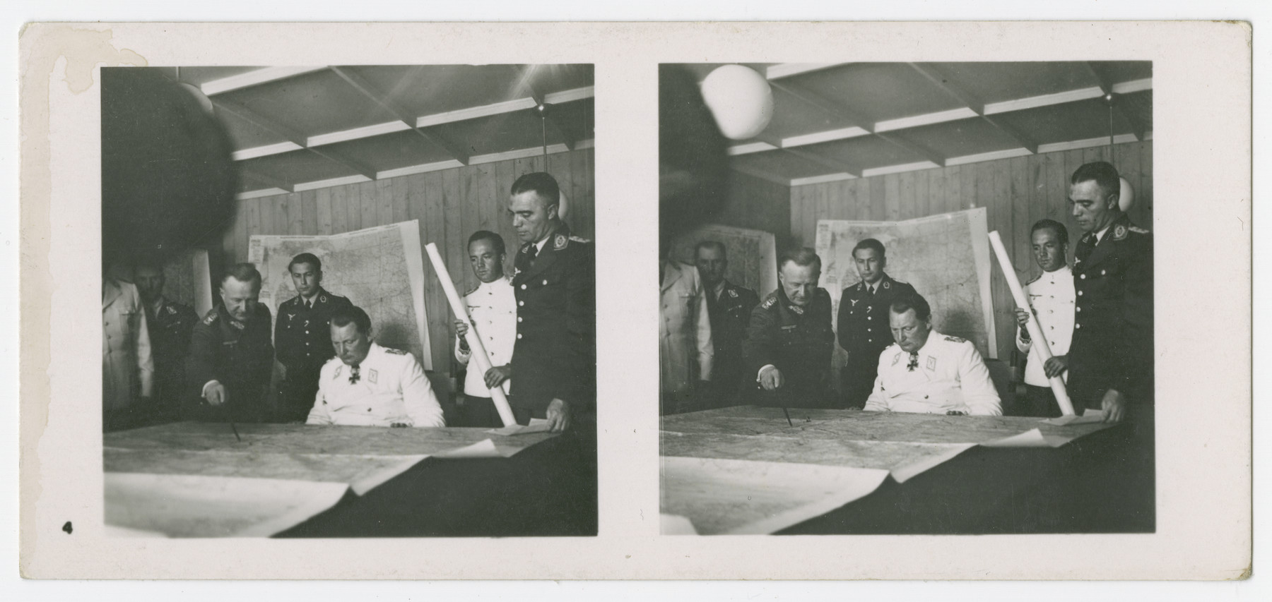 A stereograph of Herman Goering studying a map with his generals.  Original caption in German reads: Am Kartentisch seines Hauptquartiers nimmt der Reichsmarschall den Vortrag eines Generals entgegen