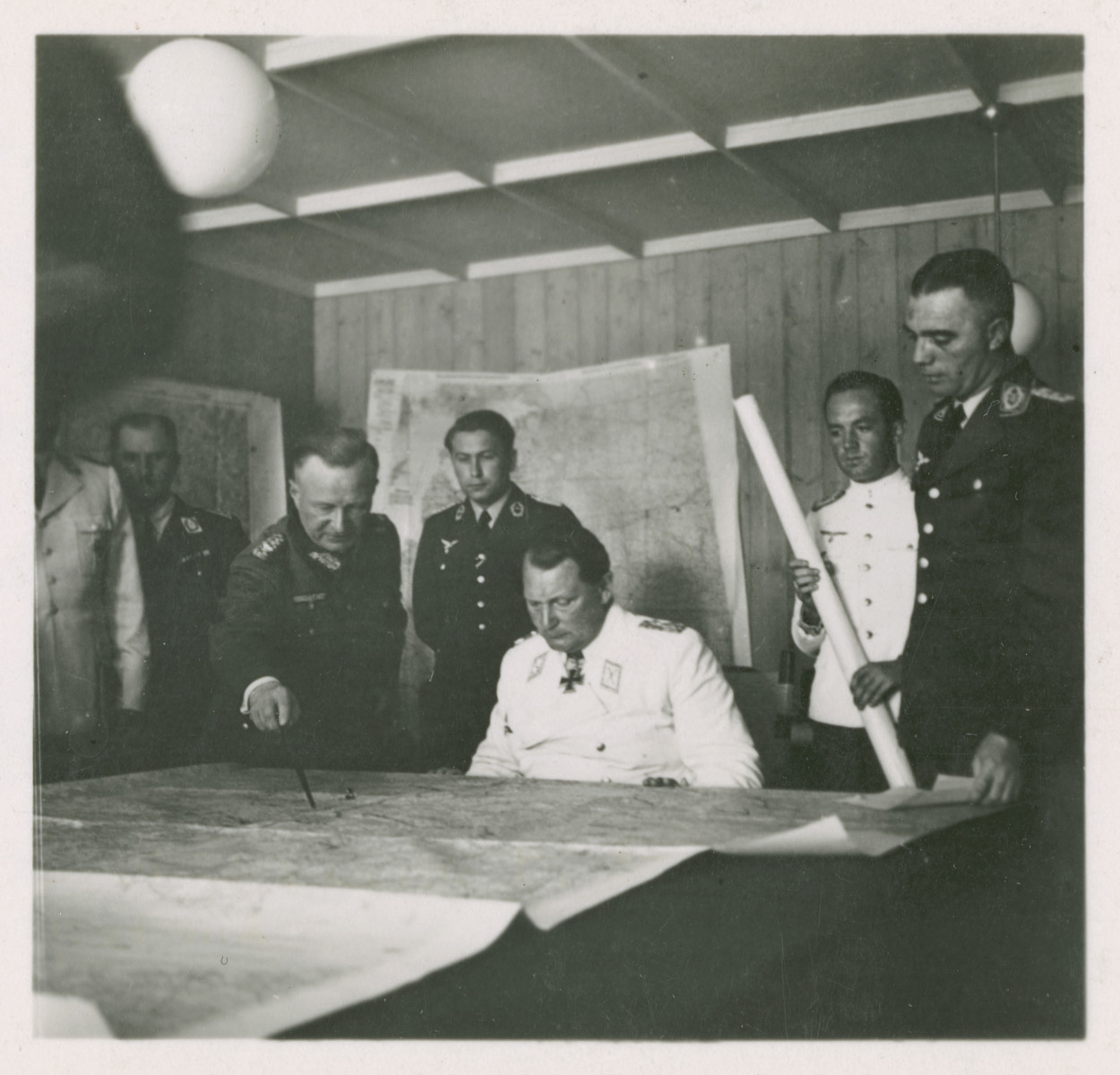 One side of a stereograph of Herman Goering studying a map with his generals.  Original caption in German reads: Am Kartentisch seines Hauptquartiers nimmt der Reichsmarschall den Vortrag eines Generals entgegen