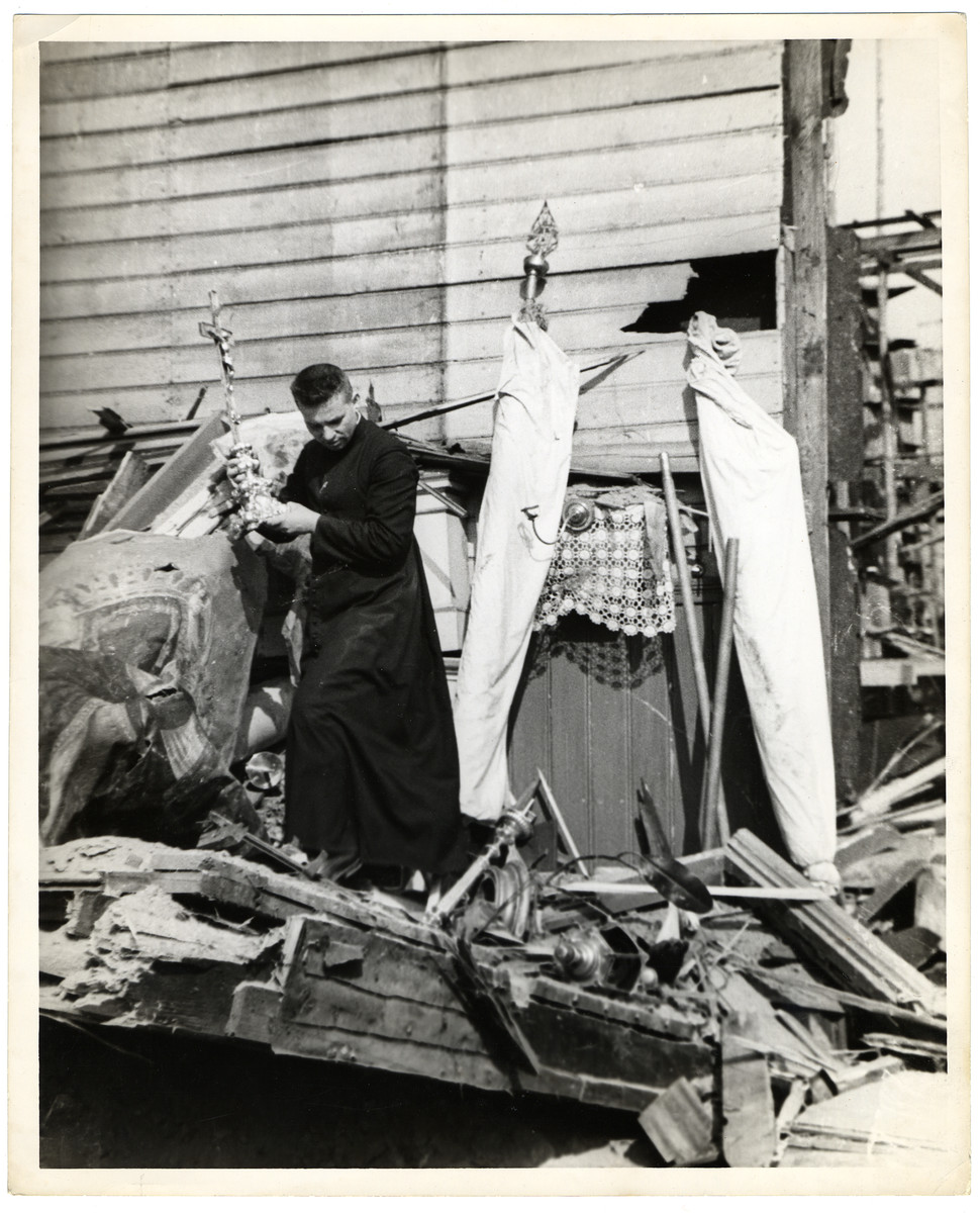 A Polish Catholic priest removes religious items (including a crucifix) from a destroyed church.