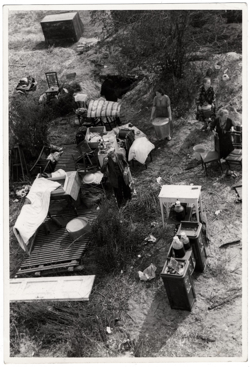 View from above of a Polish family performing their daily chores amidst the remnants of their household furnishings that they have reassembled outside the charred ruins of their home in Warsaw.