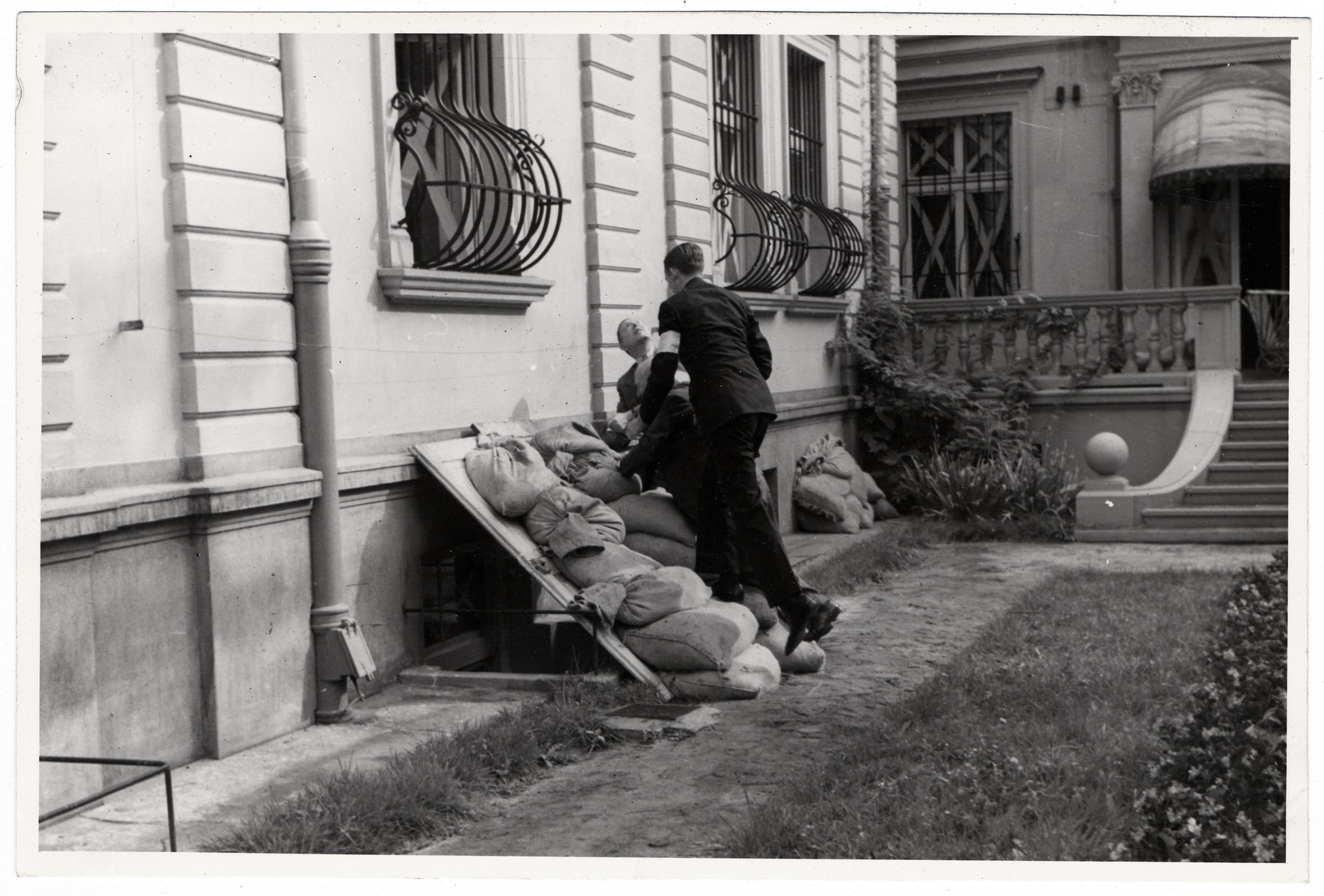 Men wearing armbands pile sand bags outside on the base of the American consulate in Warsaw to protect it from German bombs.