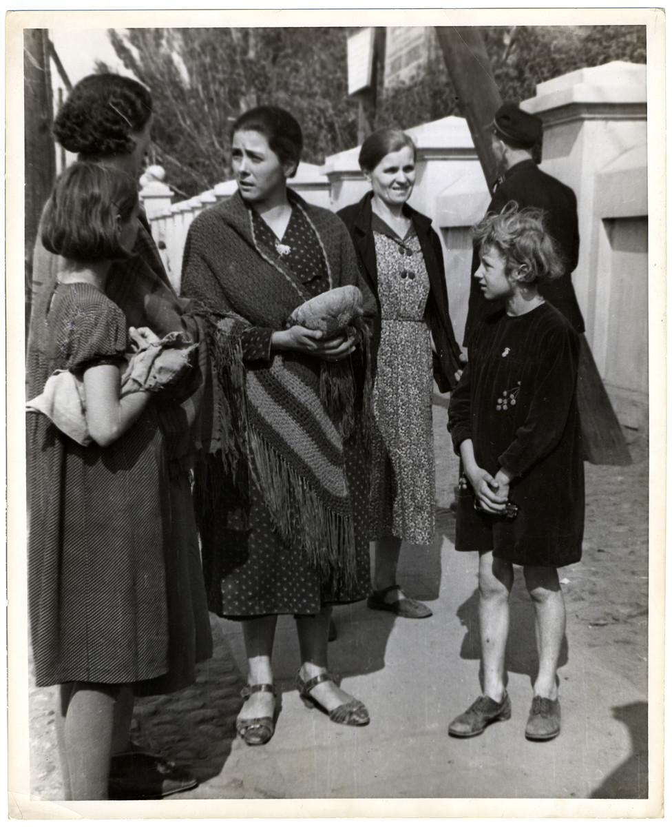 A group of Polish women and children gather on the street during the Siege of Warsaw - the woman in the center is holding a loaf of bread.