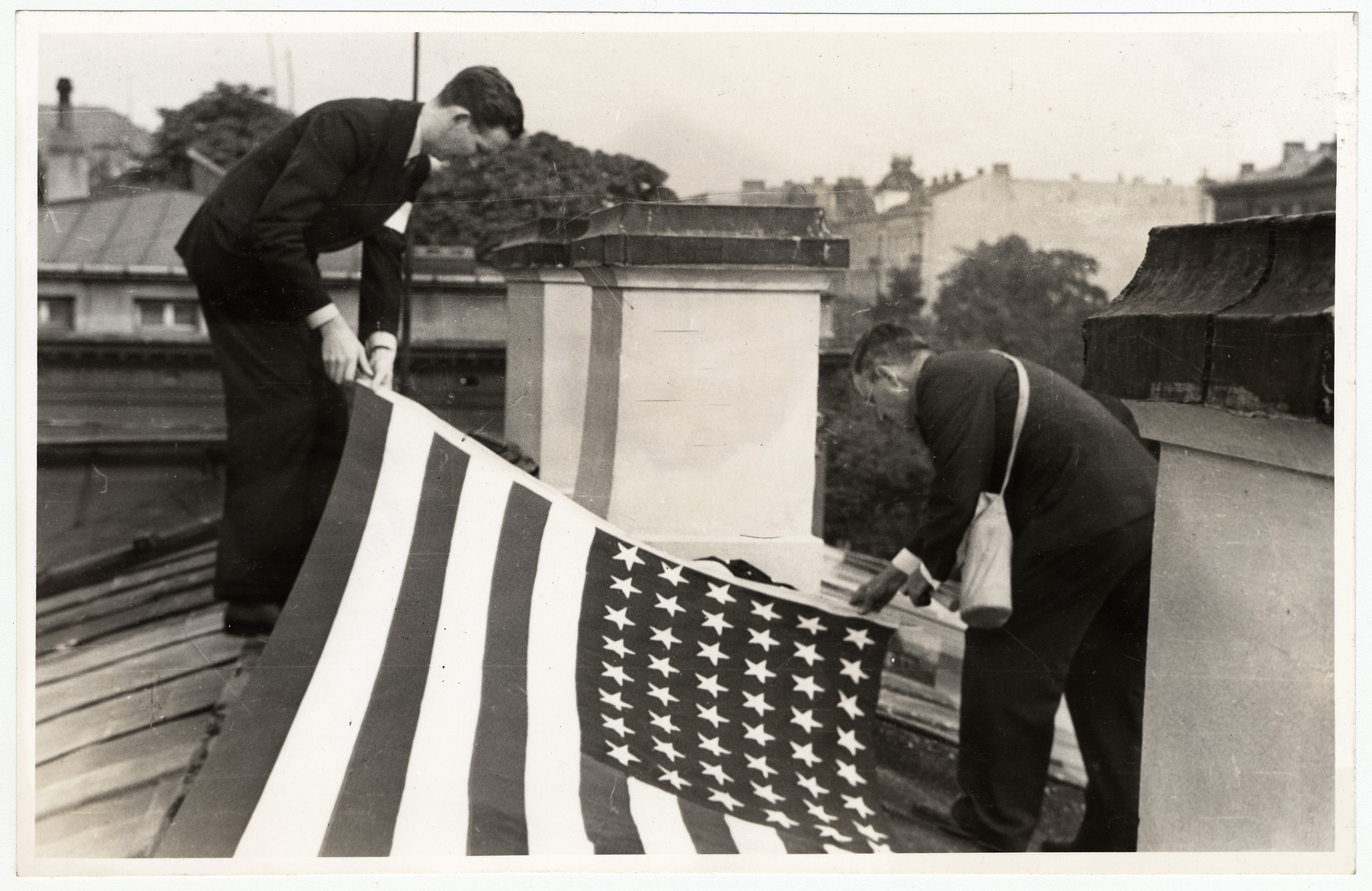 Two men unfurl a large American flag on the roof of the American Consulate.