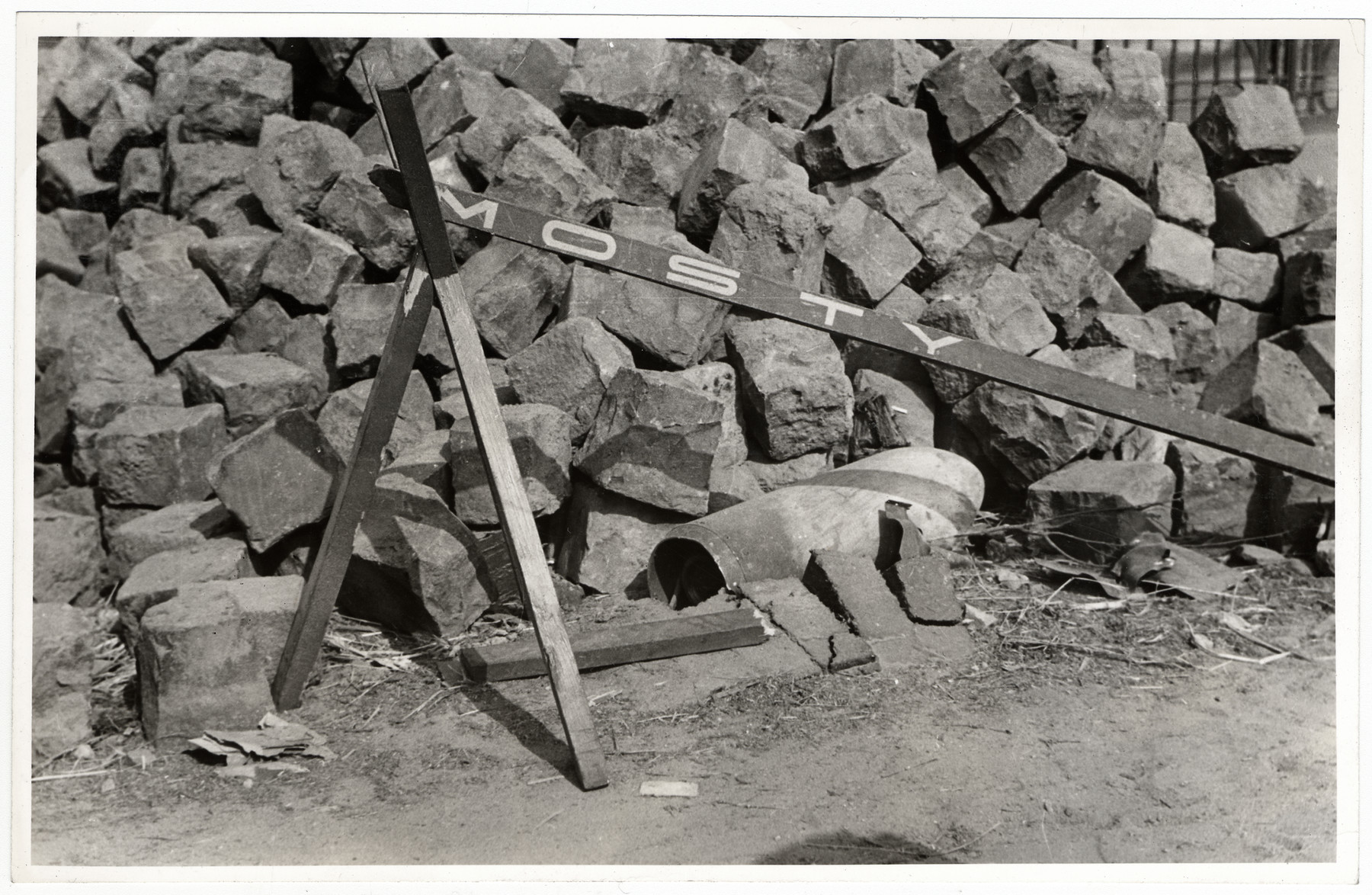 View of [what is probably the casing of a German bomb] lying next to a pile of bricks in besieged Warsaw.