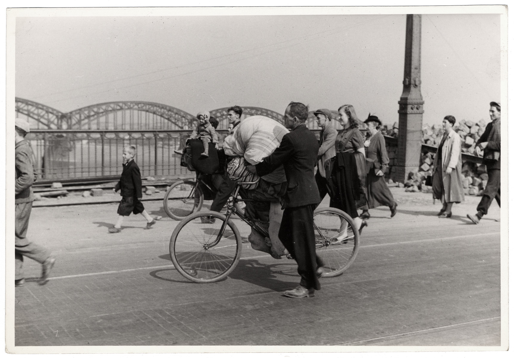 Pedestrians cross a bridge during the siege of Warsaw; one Polish man in the center carries bedding on a bicycle.