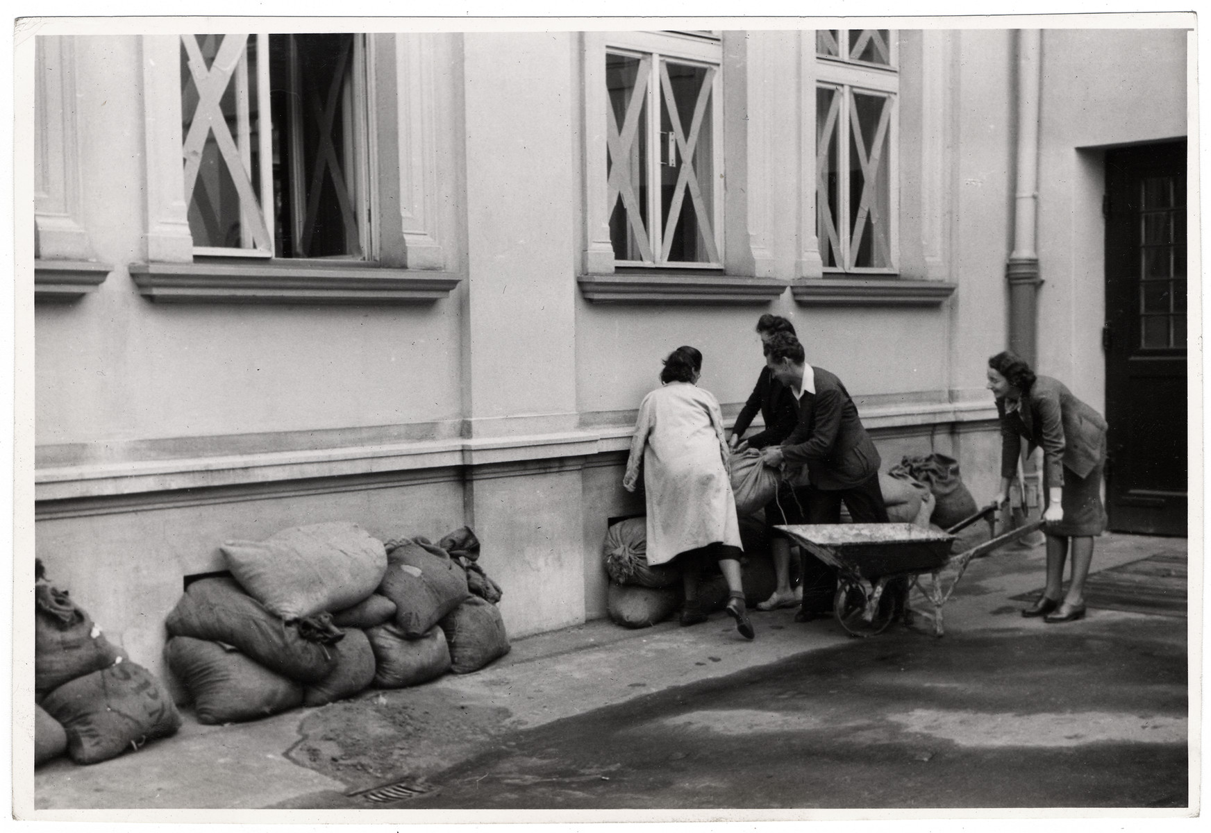 Men and women pile sand bags outside on the base of the American consulate in Warsaw to protect it from German bombs.