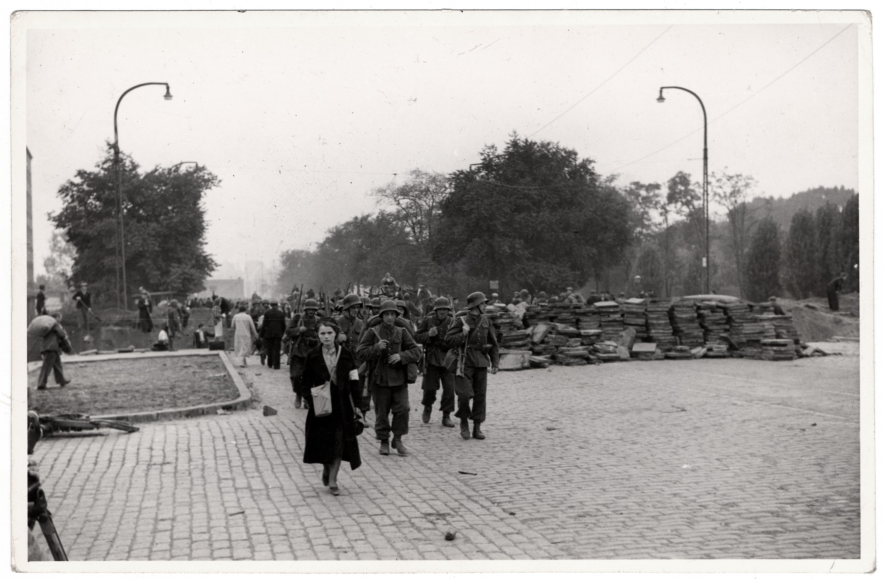 Polish civilians and soldier walk through defenses built during the Siege of Warsaw to slow the advance of the German army.