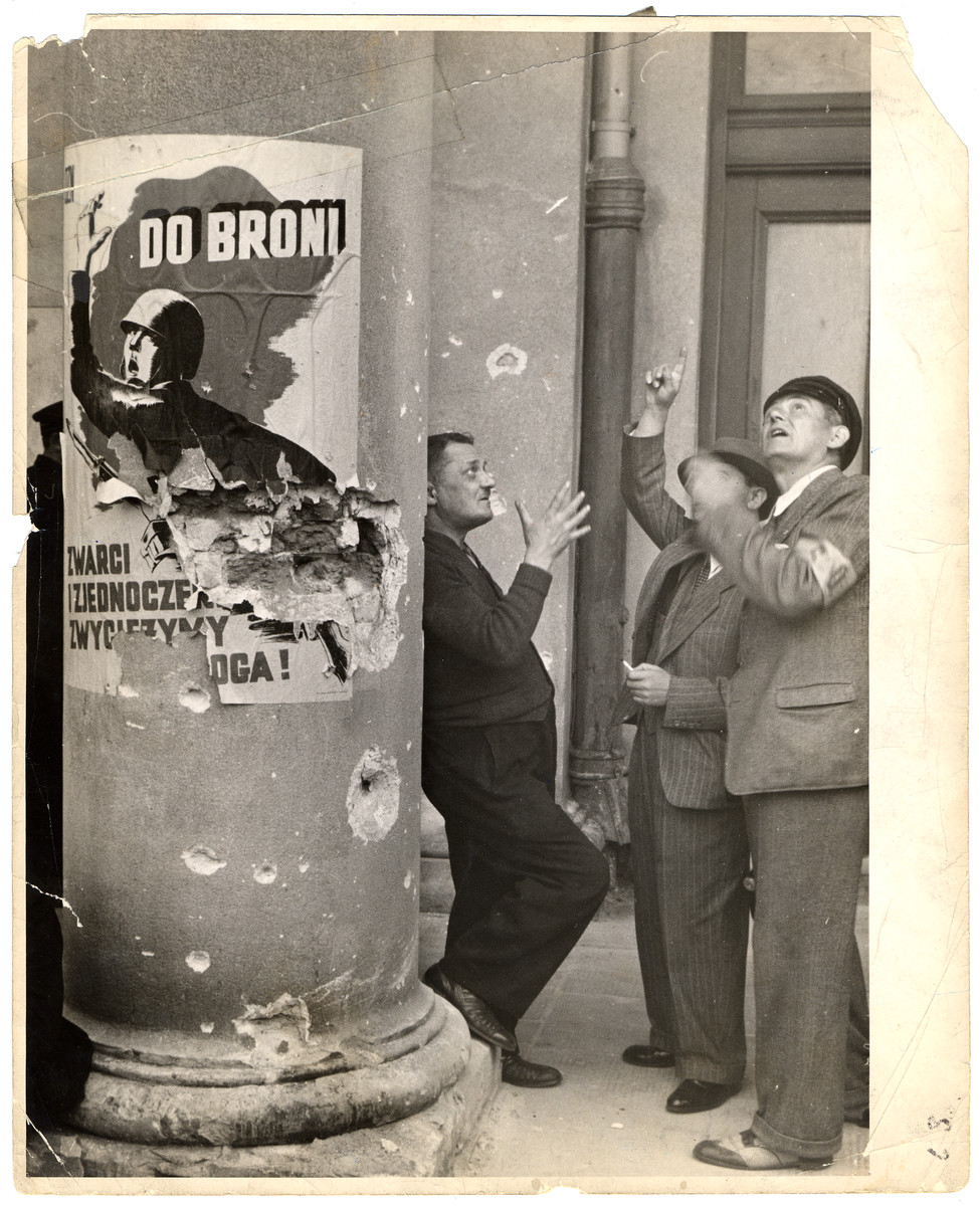 "Three volunteer policemen (strag obywatelska) stand outside the opera house in besieged Warsaw. On the column next to the men is a propaganda poster that says: ""To Arms. United We Will Defeat the Enemy!"""