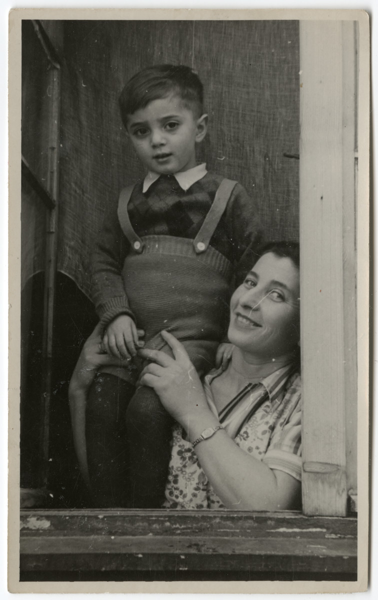Close-up portrait of a woman holding up her child by a window in the Schlachtensee displaced persons' camp.  Pictured are Mrs. Melzer and her son Moshe (b. 8/2/43).