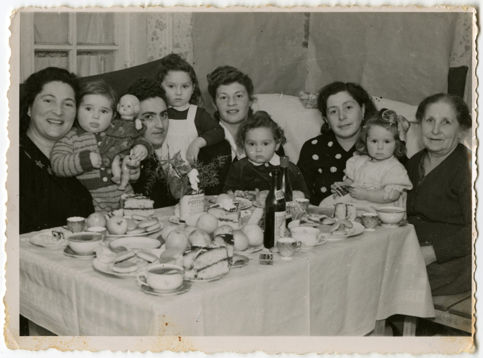 Mothers and toddlers gather around a festive table in the Schlachtensee displaced persons' camp.