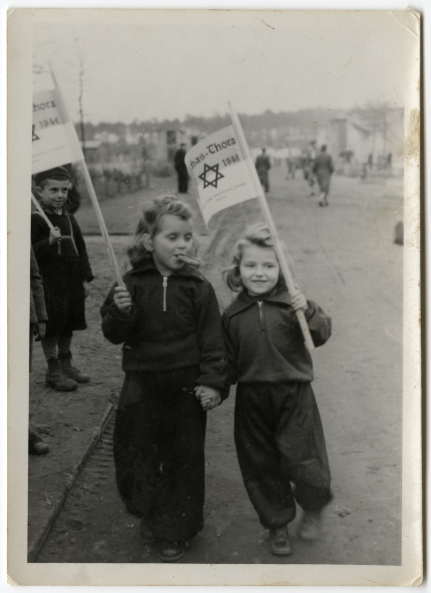 Two young girls walk down a road in the Schlachtensee displaced persons' camp carrying Simchat Torah flags.  Clara Fineklsztajn is on the left.