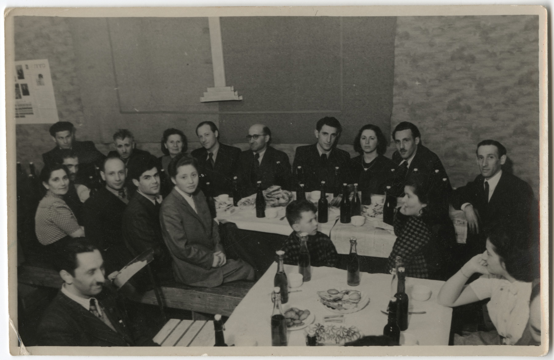 """U.S. Army chaplains host a meal for the Hebrew school in the Schlachtensee displaced persons' camp.  The original caption reads: """"First taste of Coca Cola US Army Rabbinate 1947."""""""