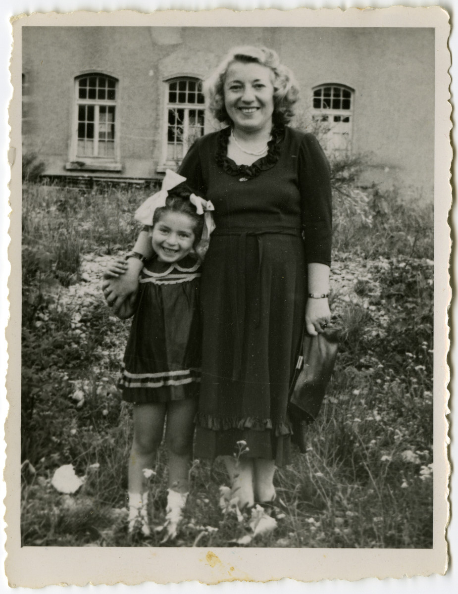 A mother and her young daughter stand in a patch of wild flowers in the Schlachtensee displaced persons' camp.