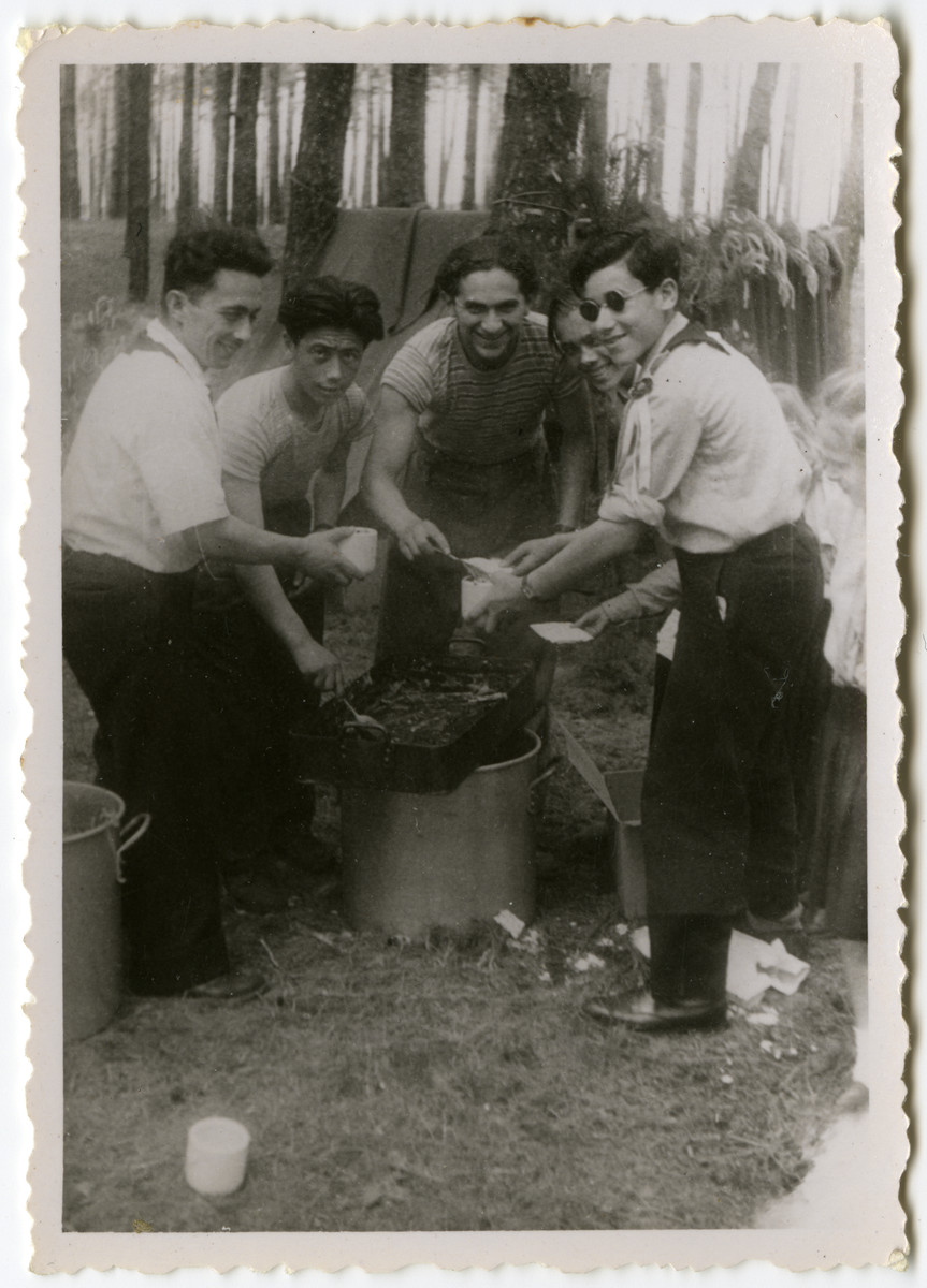 Five members of Hashomer Hatzair cook outside on a camping excursion.