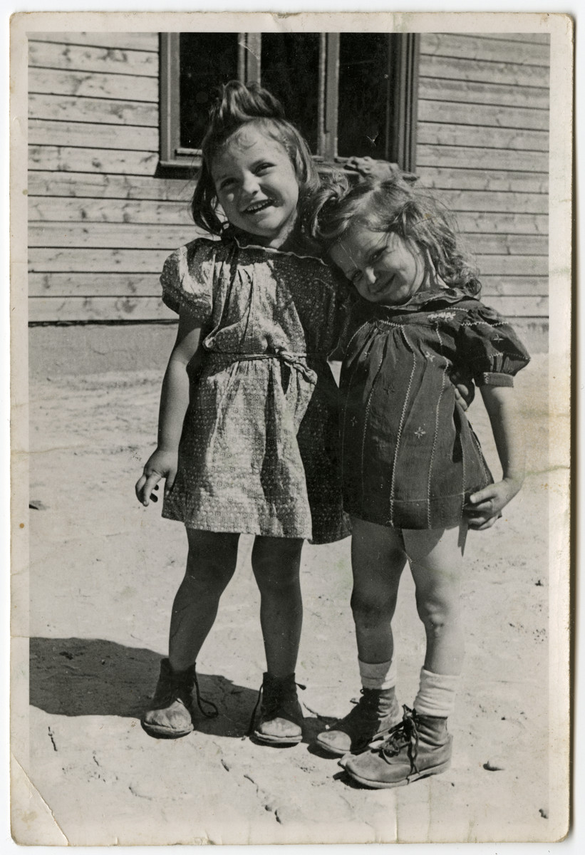 Two young girls pose outside a building in the Schlachtensee displaced persons' camp.  Clara Fineklsztajn is on the left.