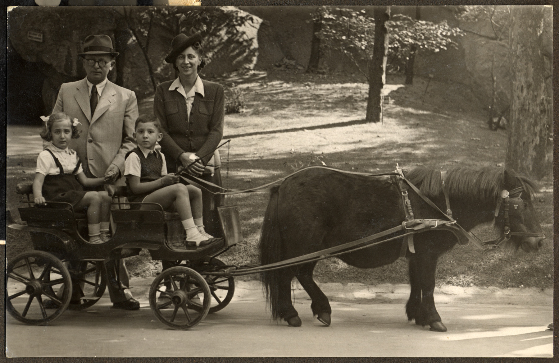 Two children go on an excursion on a pony cart in the zoo.  Pictured in the cart are Manny Mandel and his cousin Yudit Krishaber.  Standing behind them are Erno Krishaber and Ella Mandel.  Shortly afterwards, Yudit perished in Auschwitz and her father Erno Krishaber perished in a Hungarian labor camp.