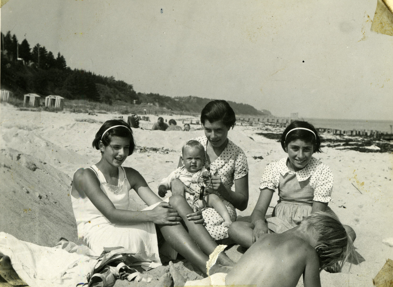 The Oestermann children relax on a beach.  Pictured from left to right are Margot, Else (holding the child of a friend), and Lilian.