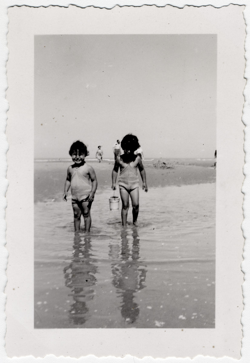 Two French Jewish sisters play at the seaside near Merlimont.  Pictured (left to right) are Jacqueline and Manuela Mendels.