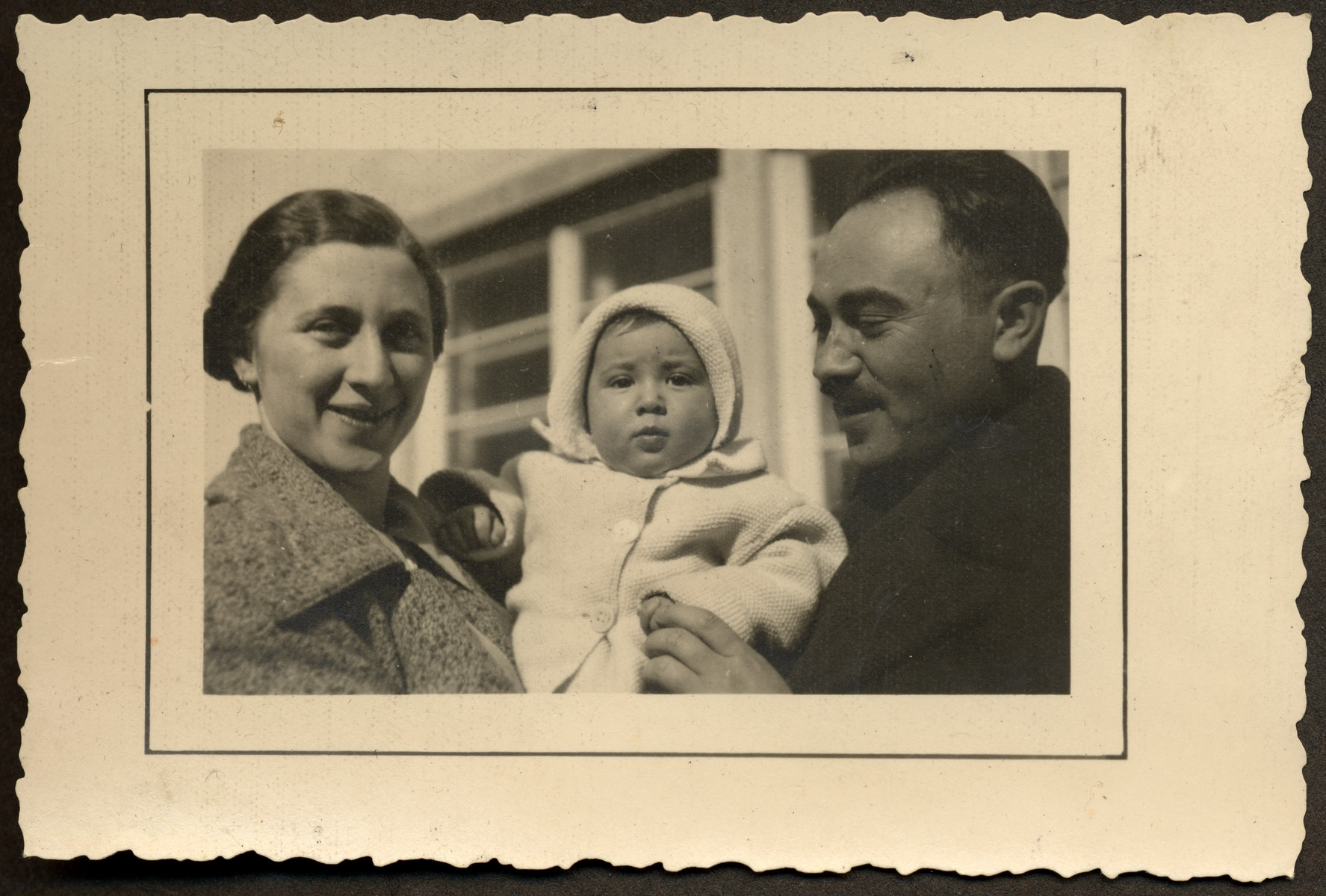 Close-up portrait of Yehuda and Ella Mandel holding their infant son, Manny.
