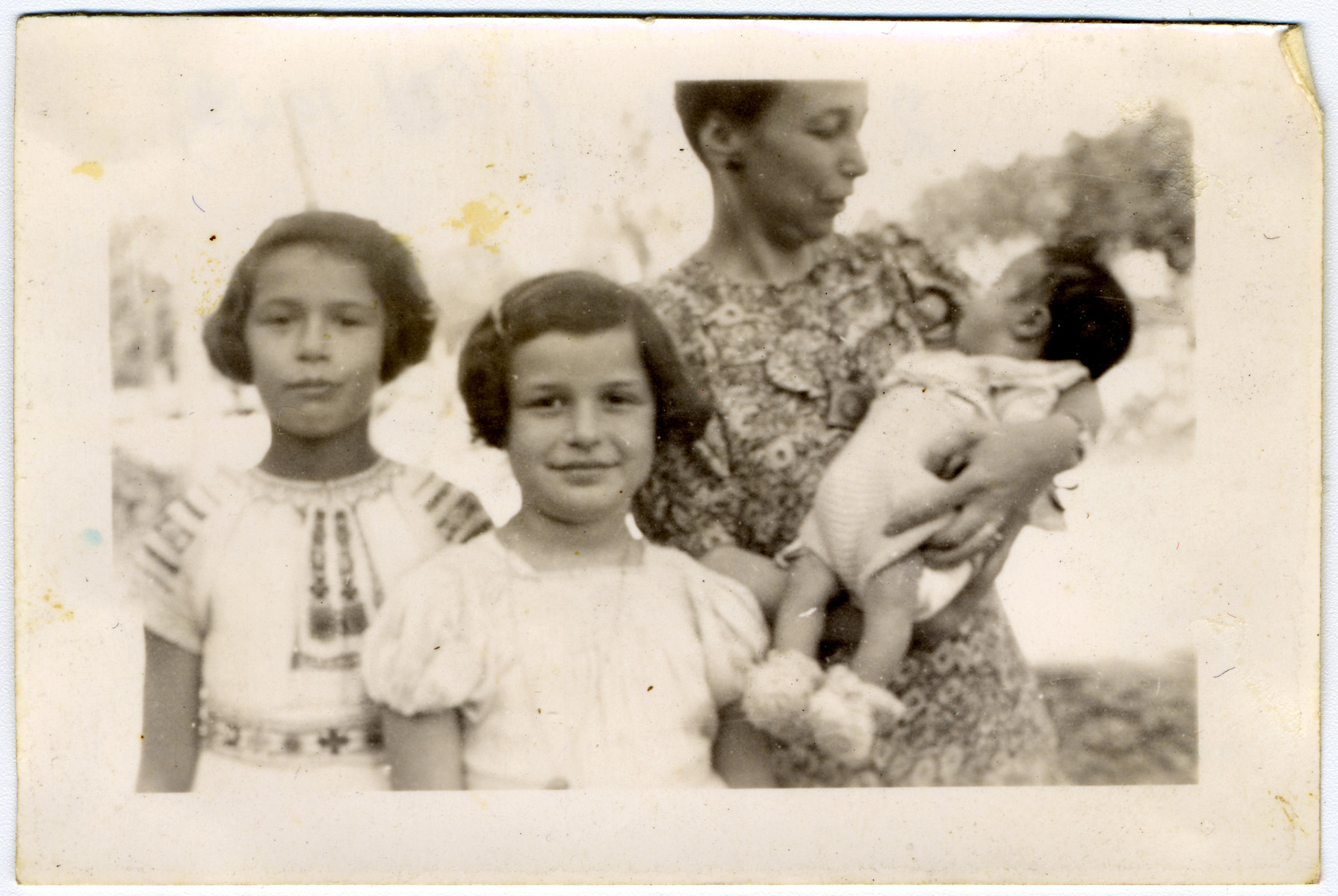 Portrait of a Jewish family in hiding.  Pictured left to right are Manuela and Jacqueline Mendels and their mother Ellen, holding their newborn brother Franklin.