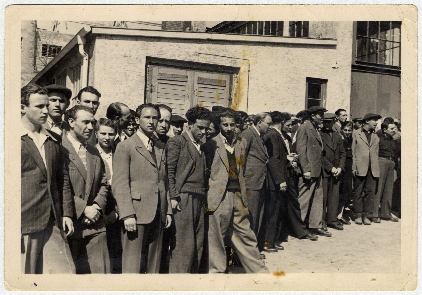 Jewish men gather in the Ziegenhain displaced persons' camp.  David Rynecki is pictured in the center (with his leg extended).