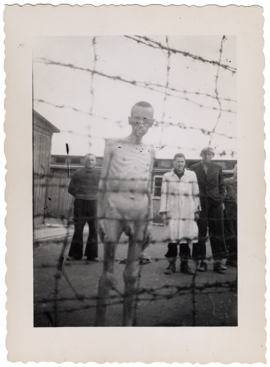 An emaciated, naked survivor stands by the barbed wire fence of the Mauthausen concentration camp after liberation.