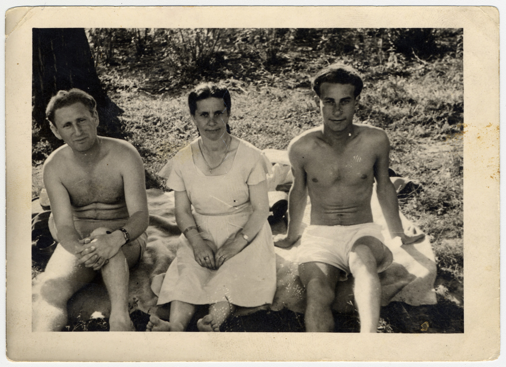 The Rynecki family relaxes outside in the Ziegenhain displaced persons' camp.  From left to right are a neighbor from Siedlce, Szendla and David Rynecki.