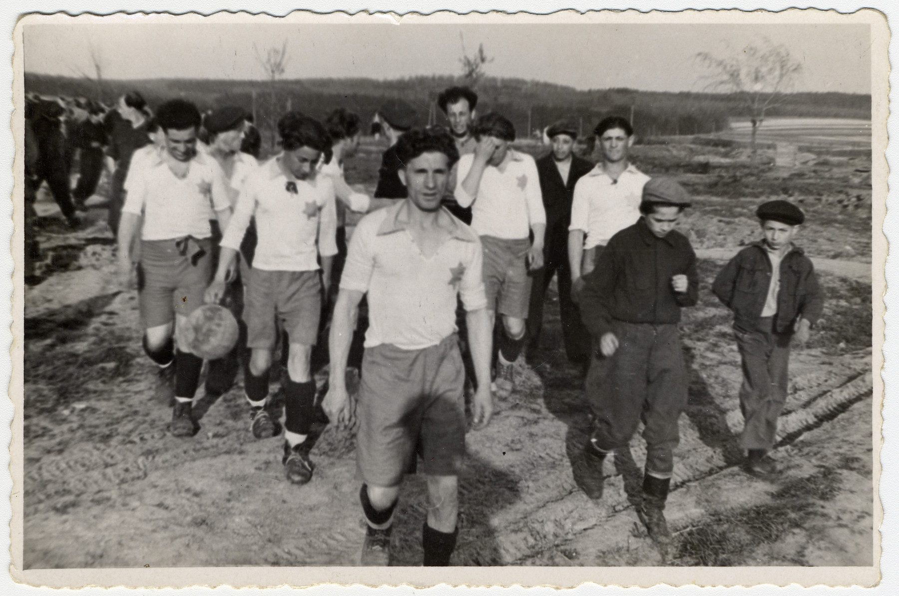 Members of Kassel displaced persons' camp soccer team walk to or from a game; their uniforms have a Star of David reminiscent of German ghetto regulations.