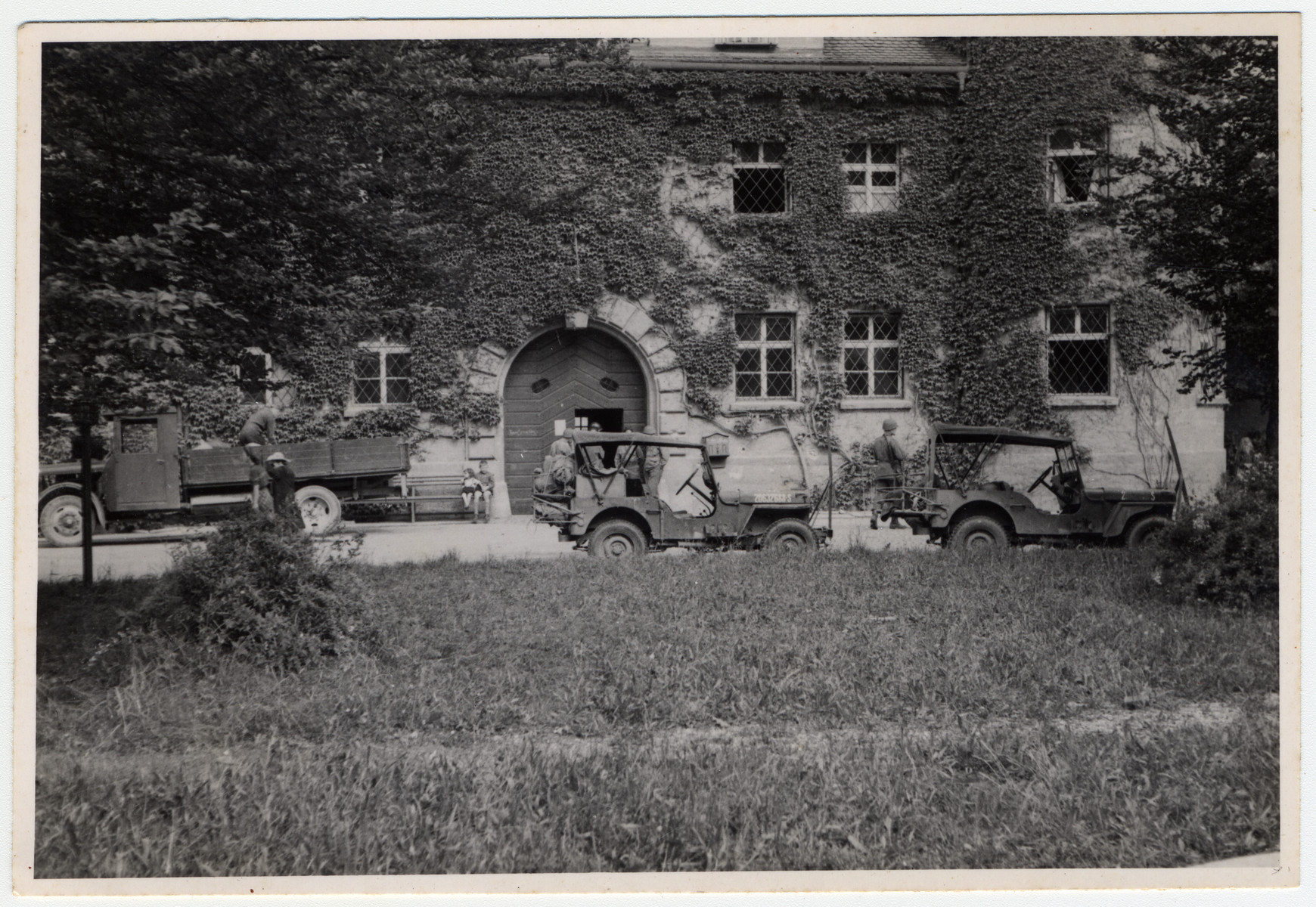 Exterior view of the front of the Landsberg prison with several military vehicles parked outside.