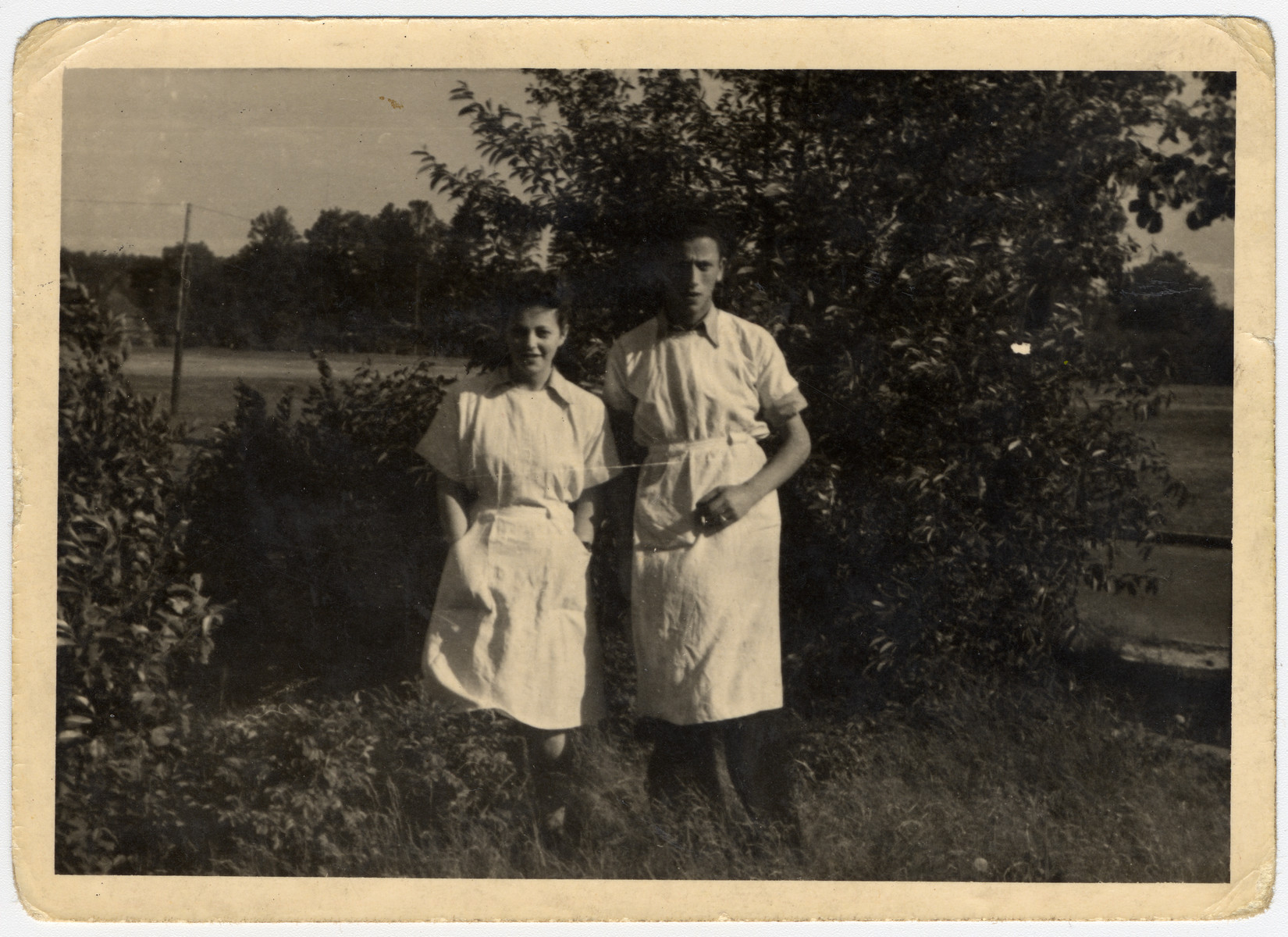 Two dental technician students stand in a garden in the Bergen-Belsen displaced persons camp.  Erno Pollak is on the right.