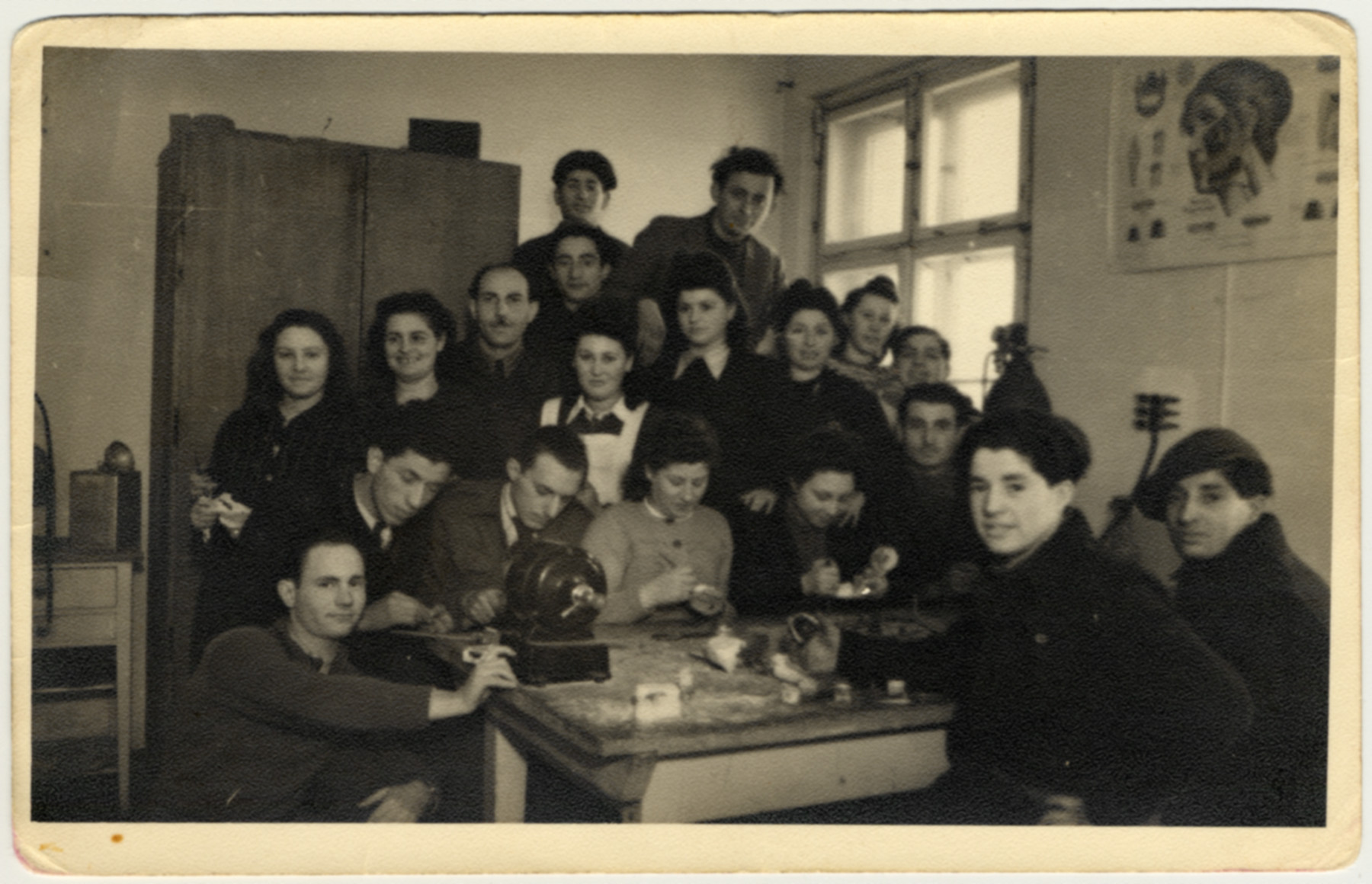 Men and women gather by a wooden work table in the ORT dental technician school in the Bergen-Belsen displaced persons camp.