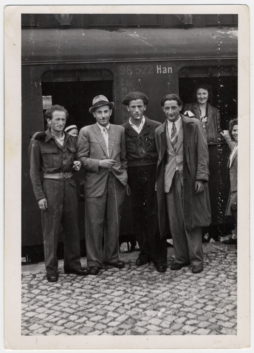 A group of Jewish men from the Bergen-Belsen displaced persons camp pose at the train station.  Erno Pollak is pictured second from the right.