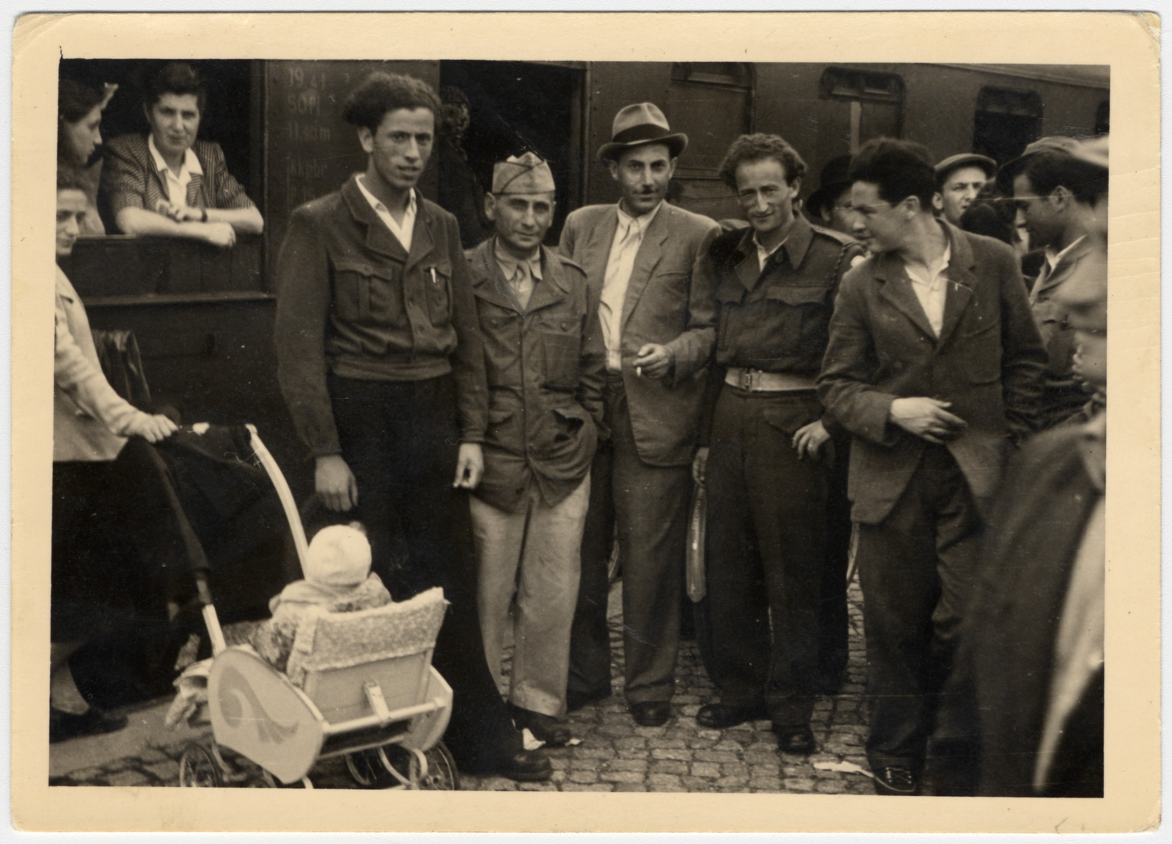 A group of Jewish men and women, one pushing a baby stroller, from the Bergen-Belsen displaced persons camp pose at the train station.  Erno Pollak is standing on the left.