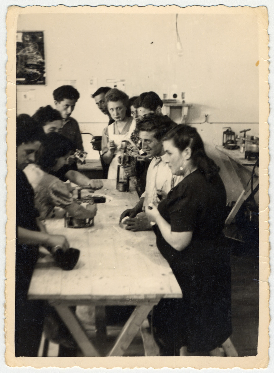 Men and women work at a wooden work table in the ORT dental technicians school in the Bergen-Belsen displaced persons camp.
