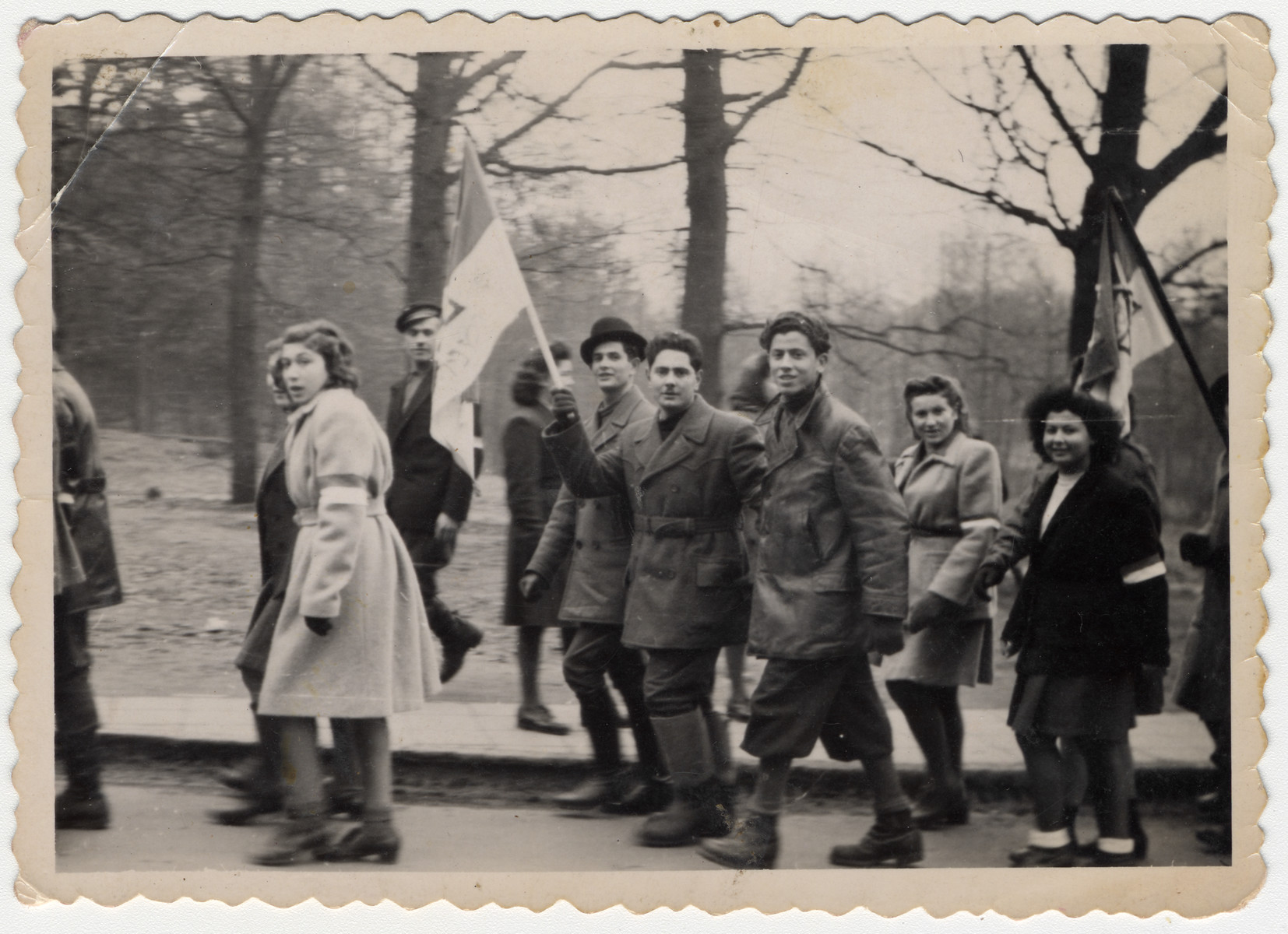 Zionist youth, one carrying a Zionist flag, march in a rally in the Bergen-Belsen displaced persons camp.