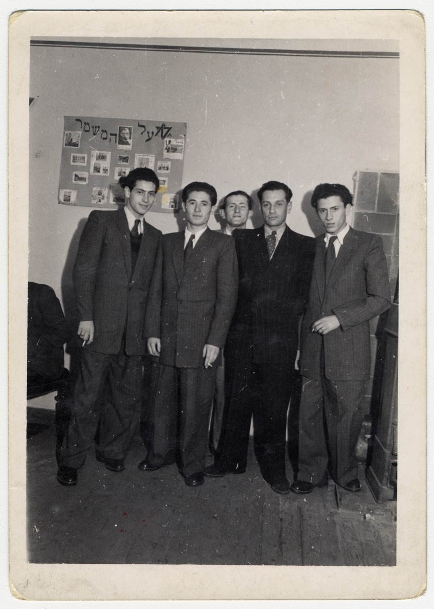 """Five young men pose in front of a Zionist photo display poster entitled """"al hamishmar"""" in the Bergen-Belsen displaced persons camp.  Erno Pollak is pictured on the far right."""