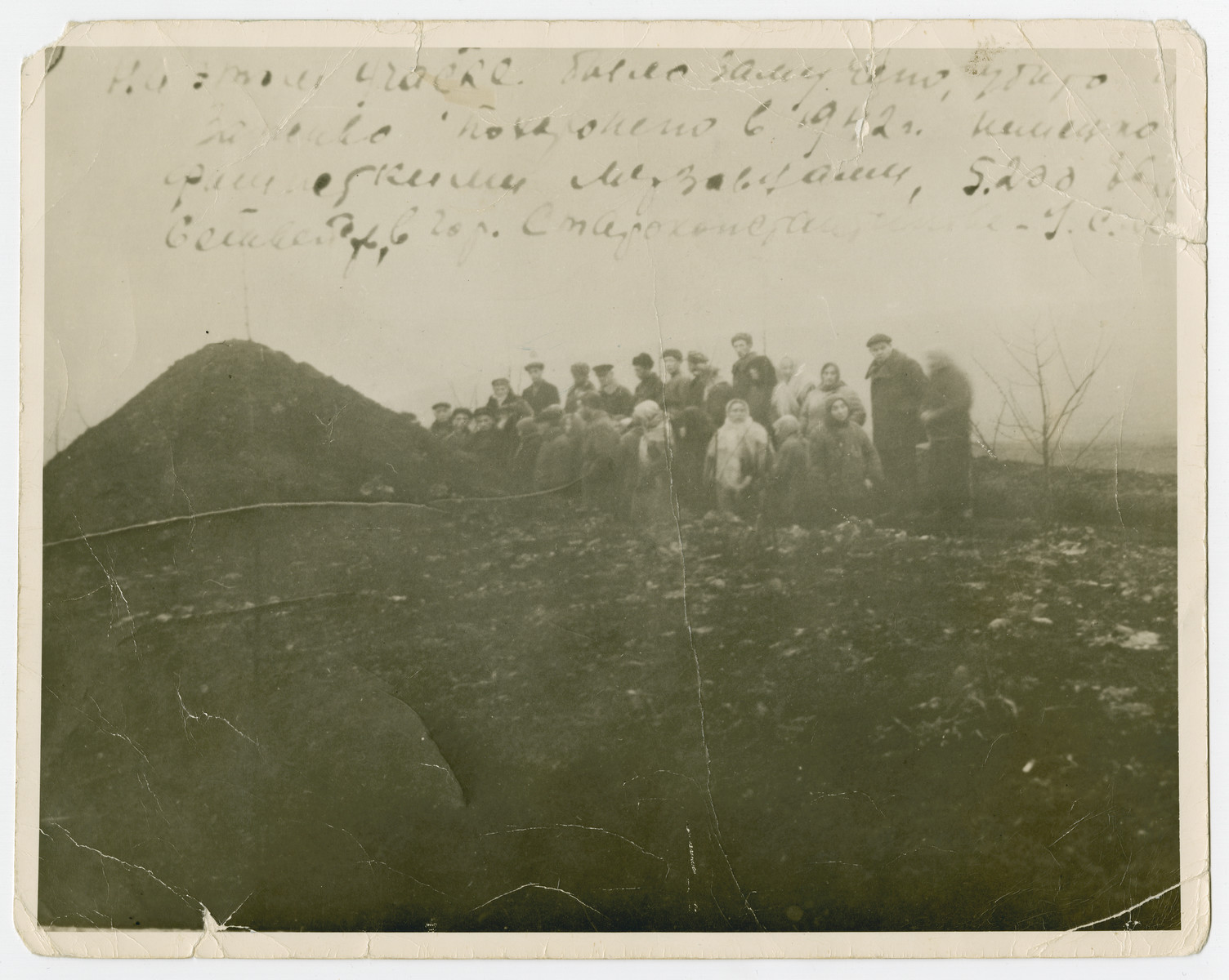 A group of people stand in a field next to a large pit. The original caption reads [On this territory, German Fascist beasts tortured, murdered, and buried alive 5200 Jewish families in the city of Starokonstantinov in 1942.]