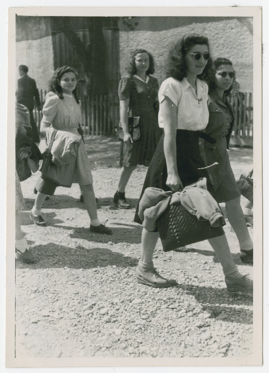 Young women walk down a street of the Eggenfelden displaced persons camp.  Vera Spitz is pictured in the front in a white shirt and sun glasses.