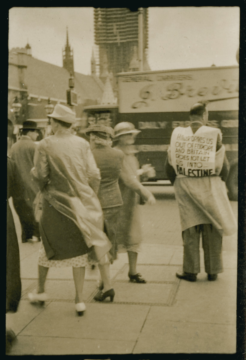 "A Jewish man demonstrates in London carrying a plackard that reads""Hitler drives us out of Europe and Britain does not let us into Palestine."""