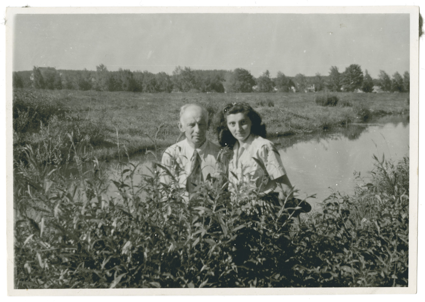 Vera Spitz poses by a stream or lake next to her father Bela.