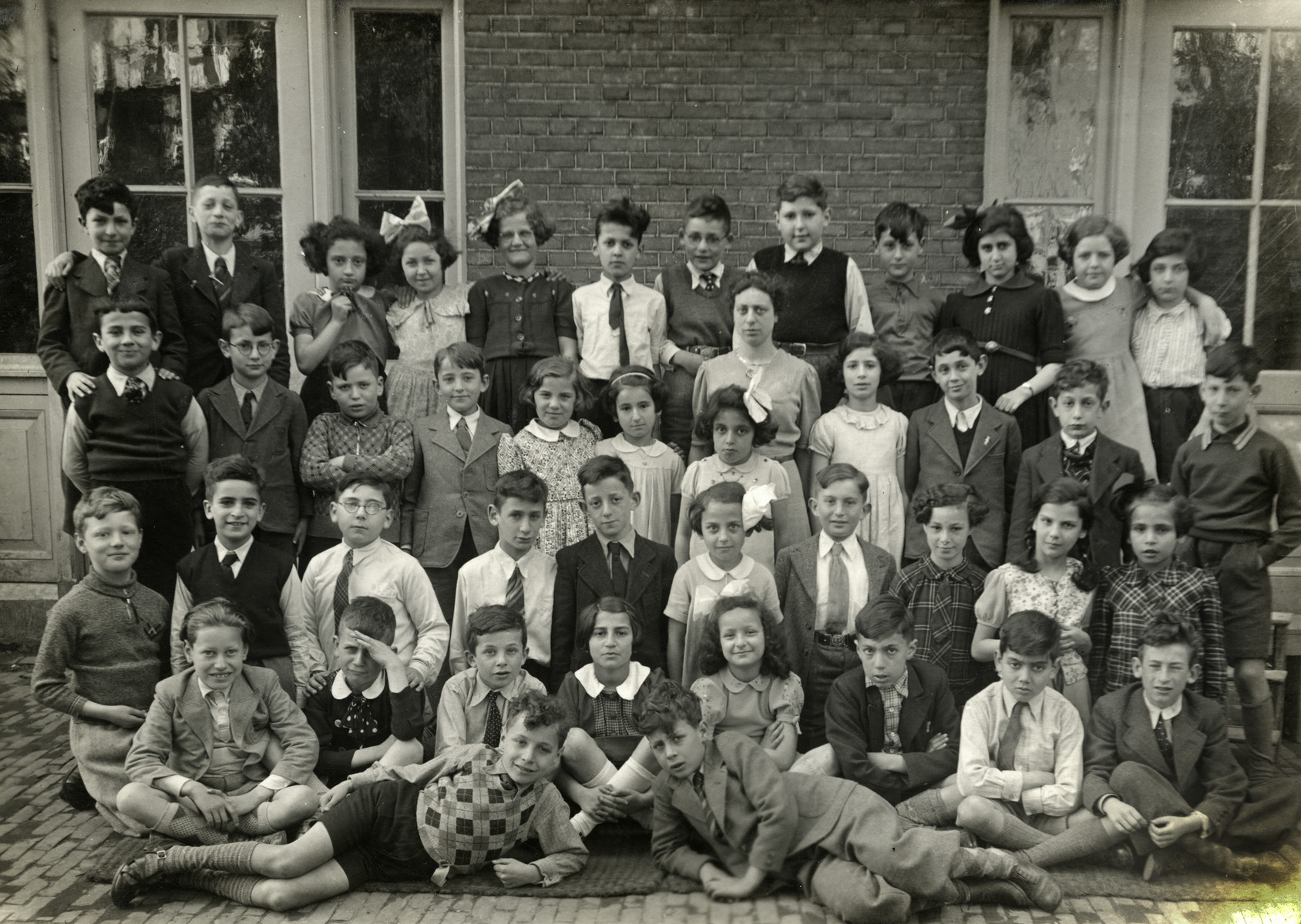 Group portrait of children in the 3rd grade of the Jewish elementary class in Amsterdam.  Among those pictured is Elchanan Tal (front row in a while shirt and tie).