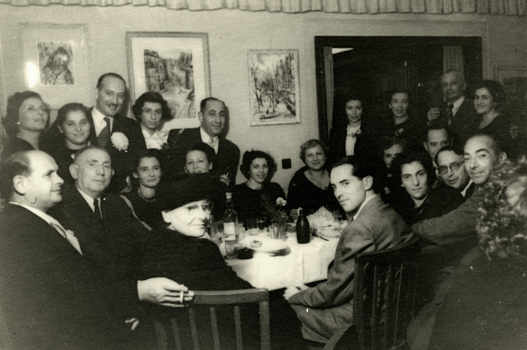 Former patisans gather for a party  in Tel Aviv after the war.  David Svirsky is seated in front at the table wearing a suit.