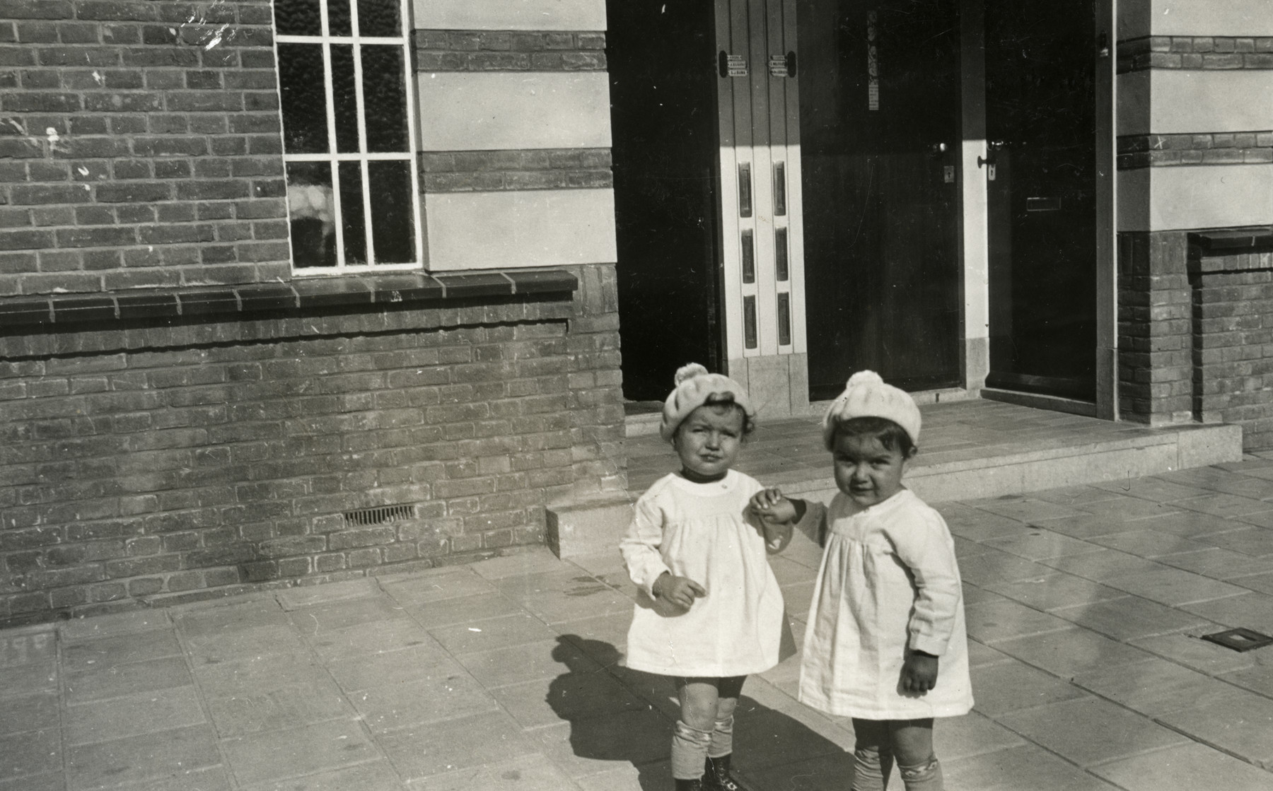 Jewish sisters, Ruth Yetta and Naomi Rivka Tal, pose in front of their family home.