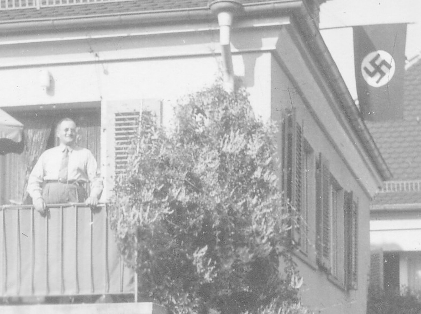 Felix Streim poses on the balcony of his apartment in Germany while a Nazi flag hangs in the background.  Felix Streim was the half-brother of Bertha Rehfisch (and great uncle of the donor).  He immigrated to New York City before WWII.