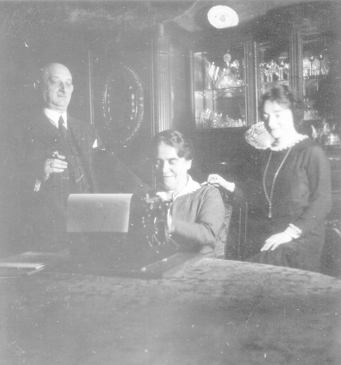 Bertha Rehfisch types at a table at home in Hannover, types with two of her family members beside her.  On the left is her husband Luis Rehfisch and on the right is their oldest daughter Elsbeth.