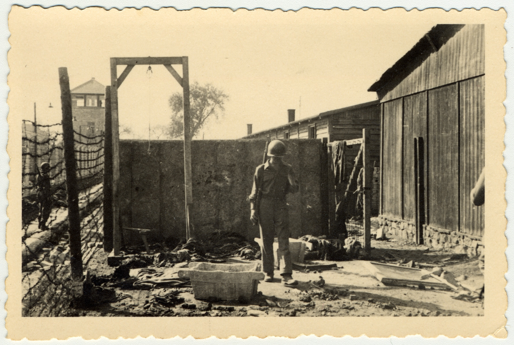 "An American soldier inspects the gallows of the Mauthausen concentration camp.  The original caption reads: ""This is one place they shot and hung the people."""