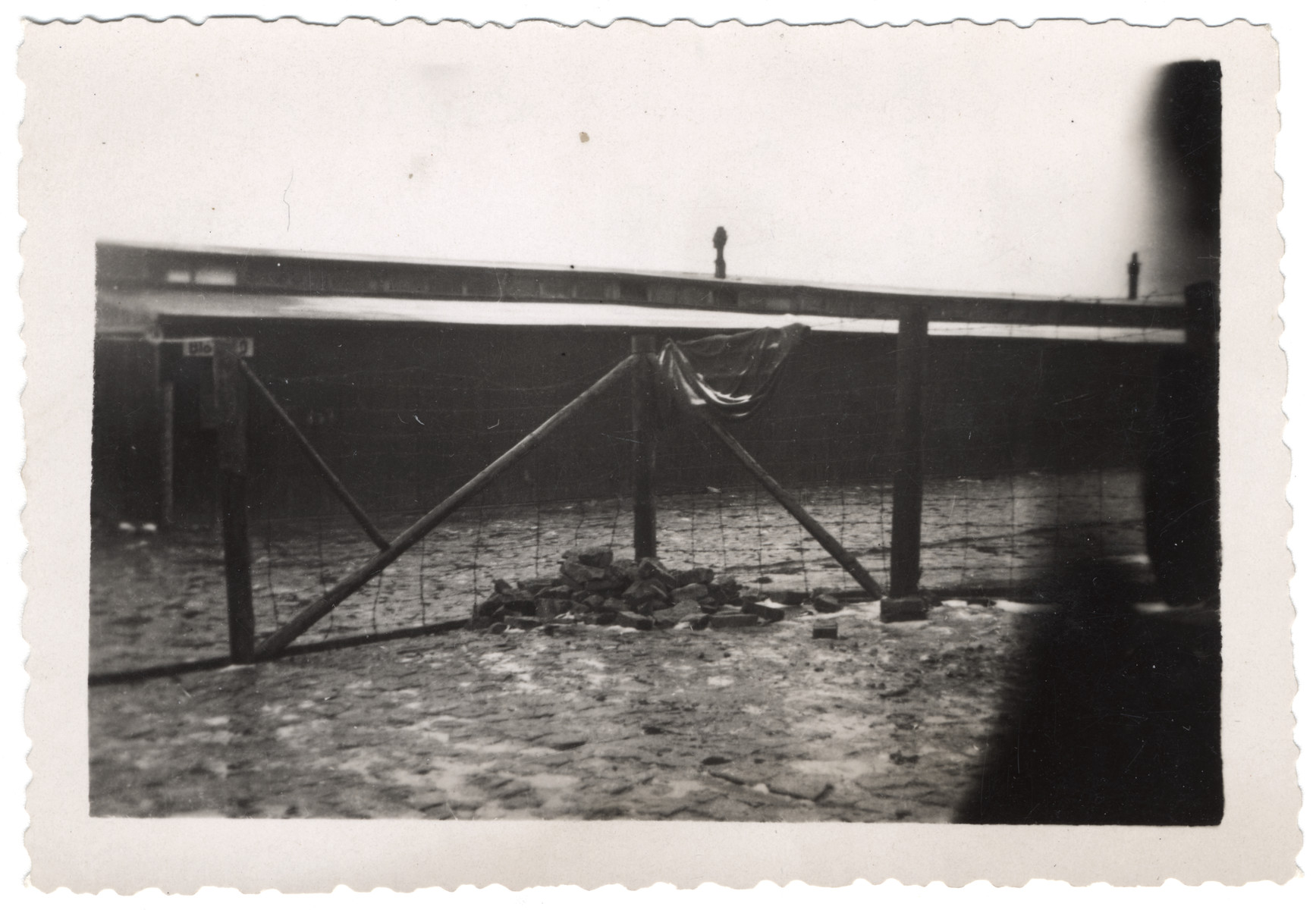 "View of a barrack and fence in Buchenwald.  The original caption reads: ""Barrack and enclosure.  Usual capacity of barracks- 1500 persons."""