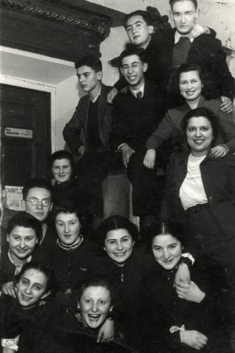 A group of young Jewish adults probably recent graduates of the Hebrew Gymnasium] gather together. for the camera.  Among those pictured are Greenholz, Mina Kurgan (survived), Esther Yalte, Nissan Katz, David Grozinski (perished), Baruch Zach (perished) and Nissan Anolik (survived).